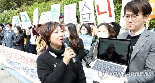 Các thành viên Minbyun tổ chức họp báo về vụ kiện của bà Nguyen Titan, người tham gia cuộc họp qua mạng (hình ảnh trong màn hình laptop) tại Seoul vào ngày 21/4. Ảnh: Yonhap