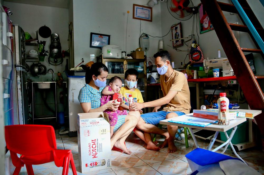 """Gia đình chị Hằng (34 tuổi) – anh Hưng (35 tuổi) có lẽ là một trong những gia đình mới nhất trong xóm trọ này. Nói là mới chứ cũng cũng ngót nghét 7 năm kể từ khi hai vợ chồng dọn về đây. Lúc có con, anh chị dành dụm mua được ít đồ trong nhà, còn bây giờ thì chị Hằng muốn bán bớt vài thứ để có thêm chút tiền trang trải cuộc sống. Chị là công nhân may, từ sau Tết, khi dịch COVID-19 xuất hiện, thu nhập của chị giảm dần, bây giờ là thất nghiệp. Còn anh Hưng chồng chị thì nhu nhập giảm một nửa vì cửa hàng cắt còn 3 ngày làm việc một tuần. Chi tiêu của cả gia đình bây giờ phụ thuộc vào số ngày lương ít ỏi của anh nên mọi thứ được gói ghém hết mức. Đưa cho con chai sữa, anh Hưng hào hứng bảo: """"Bữa nay được uống sữa ngon và đủ chất rồi nha con"""". Ảnh: Nuifood cung cấp"""