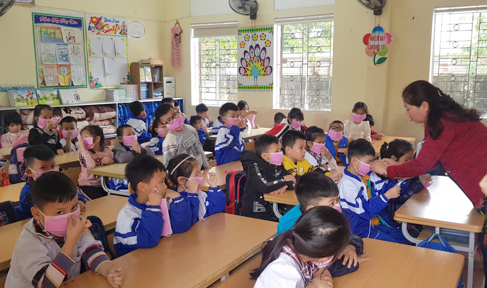 Các em học sinh tiểu học ở Nghệ An được giáo viên hưỡng dẫn đeo khẩu trang