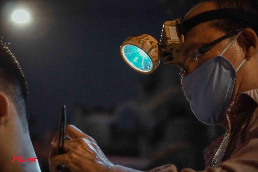 Điểm hớt tóc vỉa hè, ban đêm nguồn sáng chủ yếu là từ chiếc đèn pin đeo trên đầu người thợ.