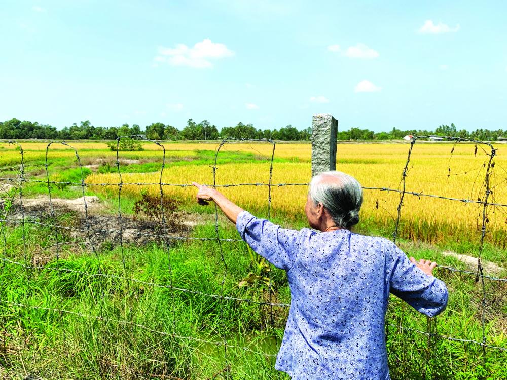 """Phía sau hàng rào kẽm gai này là dự án trại giống thủy sản chất lượng cao của Công ty TNHH Biofeed, bị """"treo"""" hơn 10 năm qua. Một số nông dân đã vào bao chiếm đất dự án để trồng lúa"""
