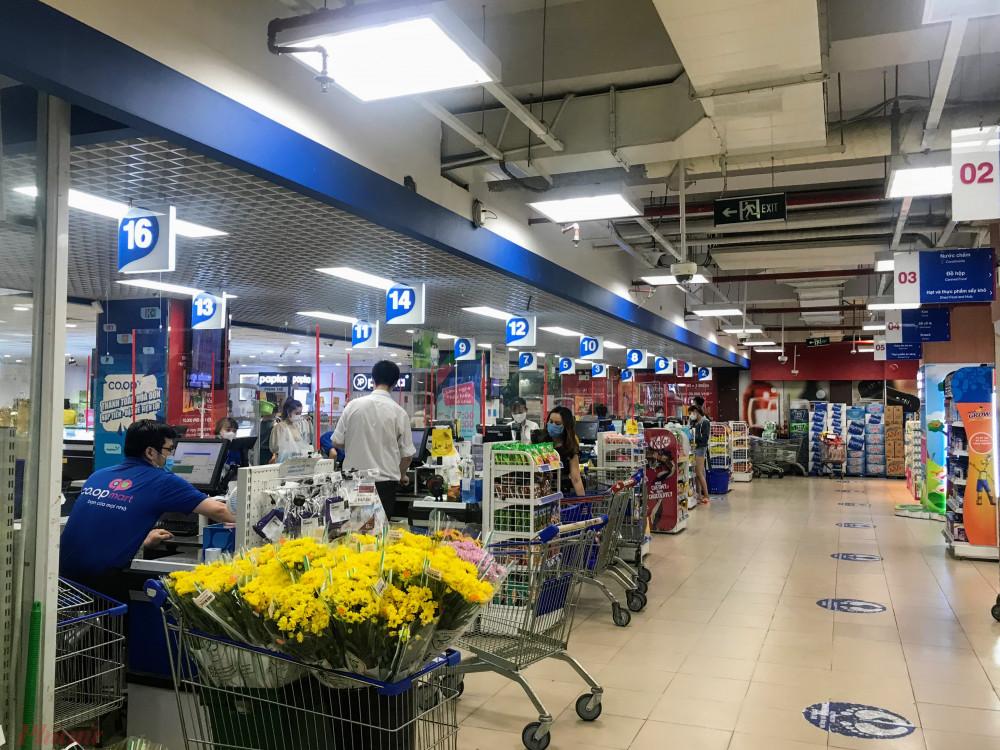 Nhân viên siêu thị ngồi chờ khách tính tiền.