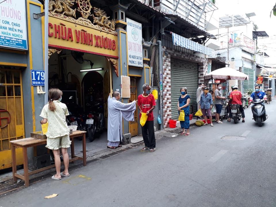 Ni sư Nhựt Thành hướng dẫn người dân tuân thủ giãn cách khi nhận gạo