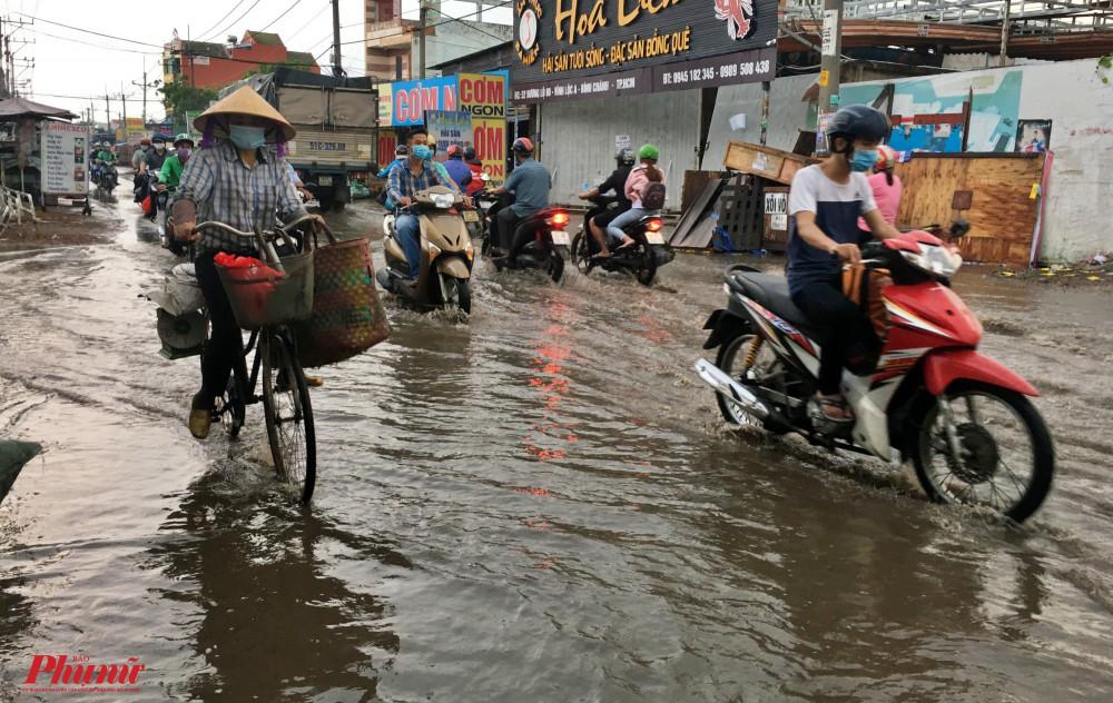 Người dân bì bõm đi qua con đường Hương lộ 80, huyện Bình Chánh bị ngập nước