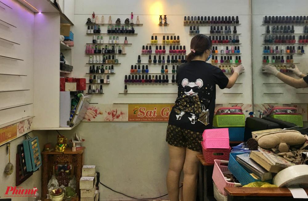 Một nhân viên của tiệm Sài Gòn nail đang tranh thủ vệ sinh, dọn dẹp đồ đạc trong thời gian vắng khách.