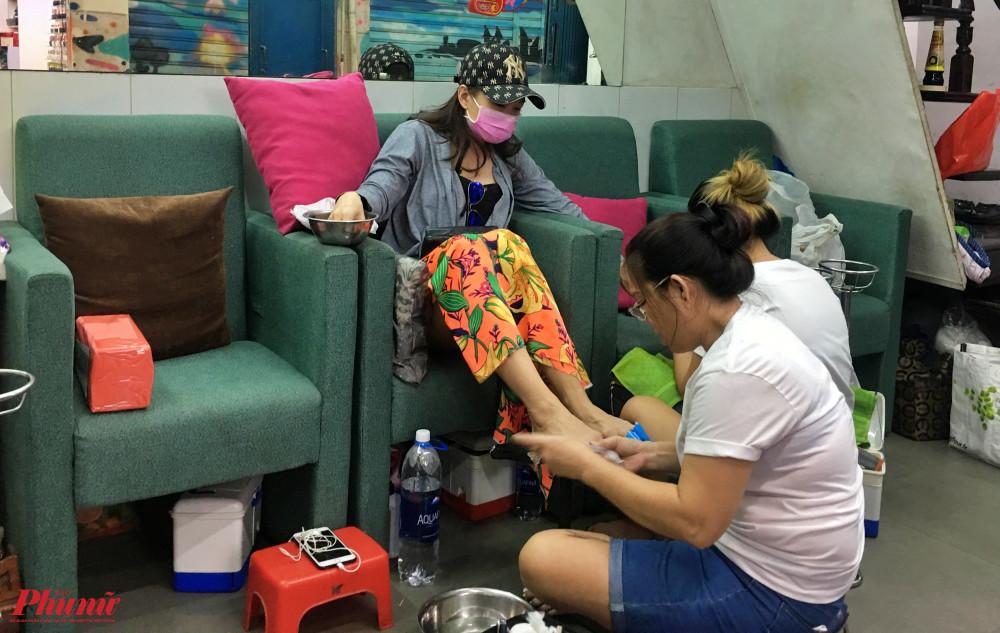 Nhân viên tiệm nail Kitty của chị Hà đang tranh thủ làm móng cho khách, chị Hà chia sẻ: Tiệm nail ở đây chủ yếu phục vụ khách nước ngoài nhưng do ảnh hưởng của dịch COVID-19 nên lượng khách cũng giảm hẳn, bây giờ mỗi ngày chỉ làm được cho khoảng 2, 3 khách rồi đóng cửa.