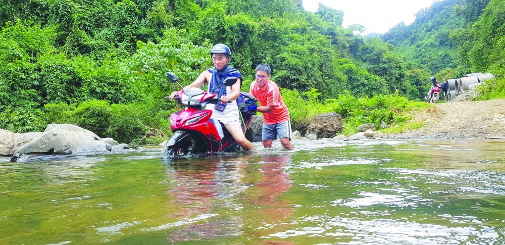 Bác sĩ Thông (người đi xe máy) trong một chuyến qua Lào tiêm chủng