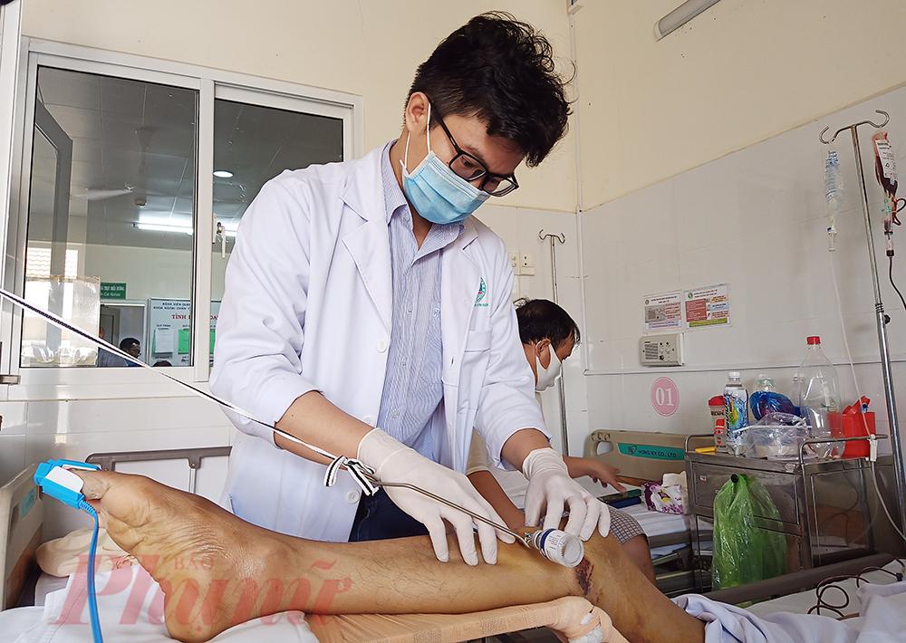 Bác sĩ Đỗ Đình Duy kiểm tra vết thương ở chân cho anh P.