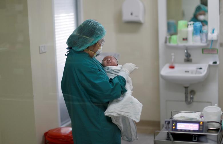 Nữ y tá đang bế một em bé 1 tháng tuổi mắc COVID-19 (cũng là bệnh nhân nhỏ tuổi nhất Thái Lan)