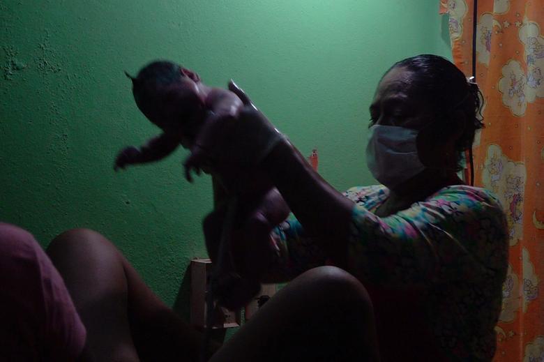 Nữ hộ sinh Juanita Zarate Solorza giúp Mariana, 29 tuổi, sinh đứa con thứ ba tại một phòng khám địa phương thay vì một bệnh viện gần đó ở Union Hidalgo, Mexico hôm 19/4.