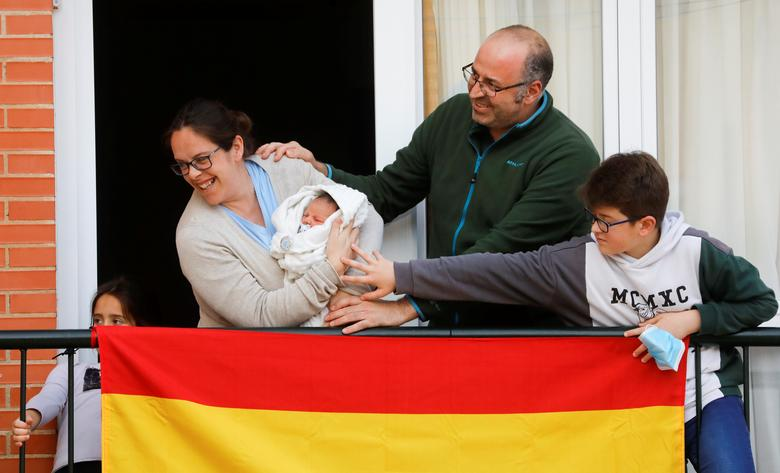 Nuria Bravo, 38 tuổi, Ronda, Tây Ban Nha) khoe con trai mới chào đời từ ban công nhà với hàng xóm.
