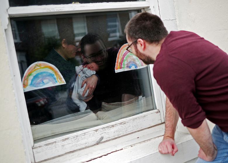 Will Watson ngắm cháu gái mới chào đời qua cửa kính khi mua đồ đến thăm và đặt trước nhà chị gái, chứ không thể vào trong do dịch bệnh diễn biến phức tạp.