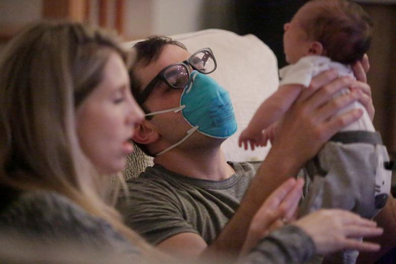 Bác sĩ khoa cấp cứu Thomas Krajewski (New Orleans, Louisiana) phải đeo khẩu trang khi bế con tại nhà.