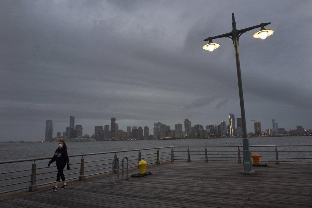 Một người phụ nữ đi bộ tại cầu cảng ở New York hôm 30/4.