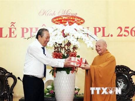 Ủy viên Bộ Chính trị, Phó Thủ tướng Thường trực Chính phủ Trương Hòa Bình (trái) tặng hoa chúc mừng Hòa thượng Thích Thiện Nhơn, Chủ tịch Hội đồng Trị sự, Giáo hội Phật giáo Việt Nam (phải) và các tăng ni, phật tử nhân Đại lễ Phật đản. (Ảnh: Xuân Khu/TTXVN)