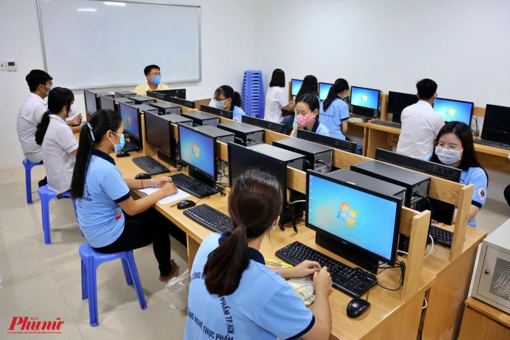 các sinh viên trong giờ thực hành bằng máy tính đều đeo khẩu trang và giữa khoảng cách an toàn đối với những người xung quanh.