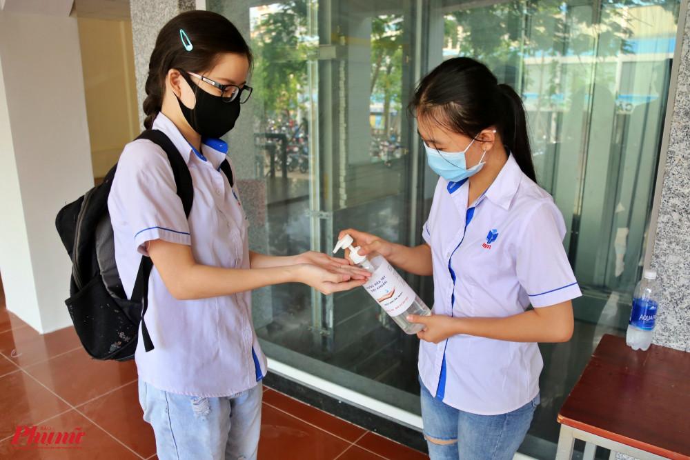 Các tình nguyện viên hỗ trợ các sinh viên thực hiện việc rửa tay bằng dung dịch sát khuẩn trước khi vào lớp học.