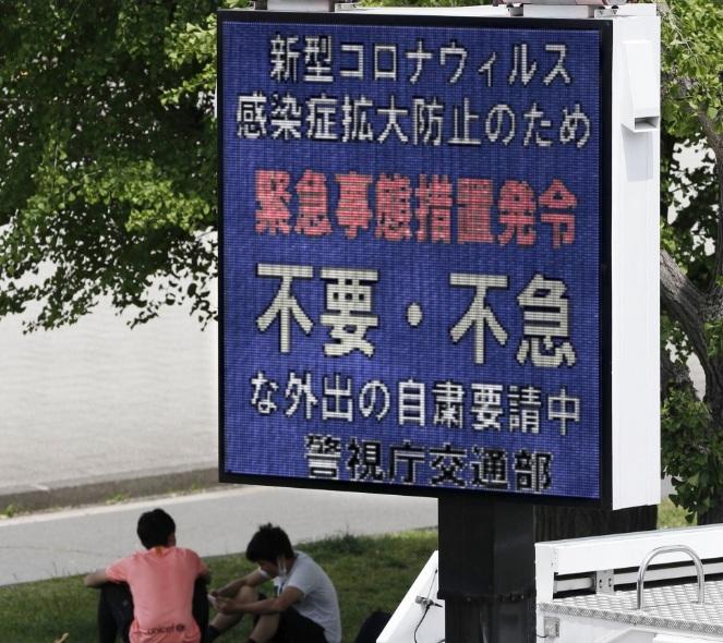 Một bảng điện tử ở Tokyo yêu cầu người dân hạn chế ra khỏi nhà trong đại dịch trừ trường hợp cần thiết.