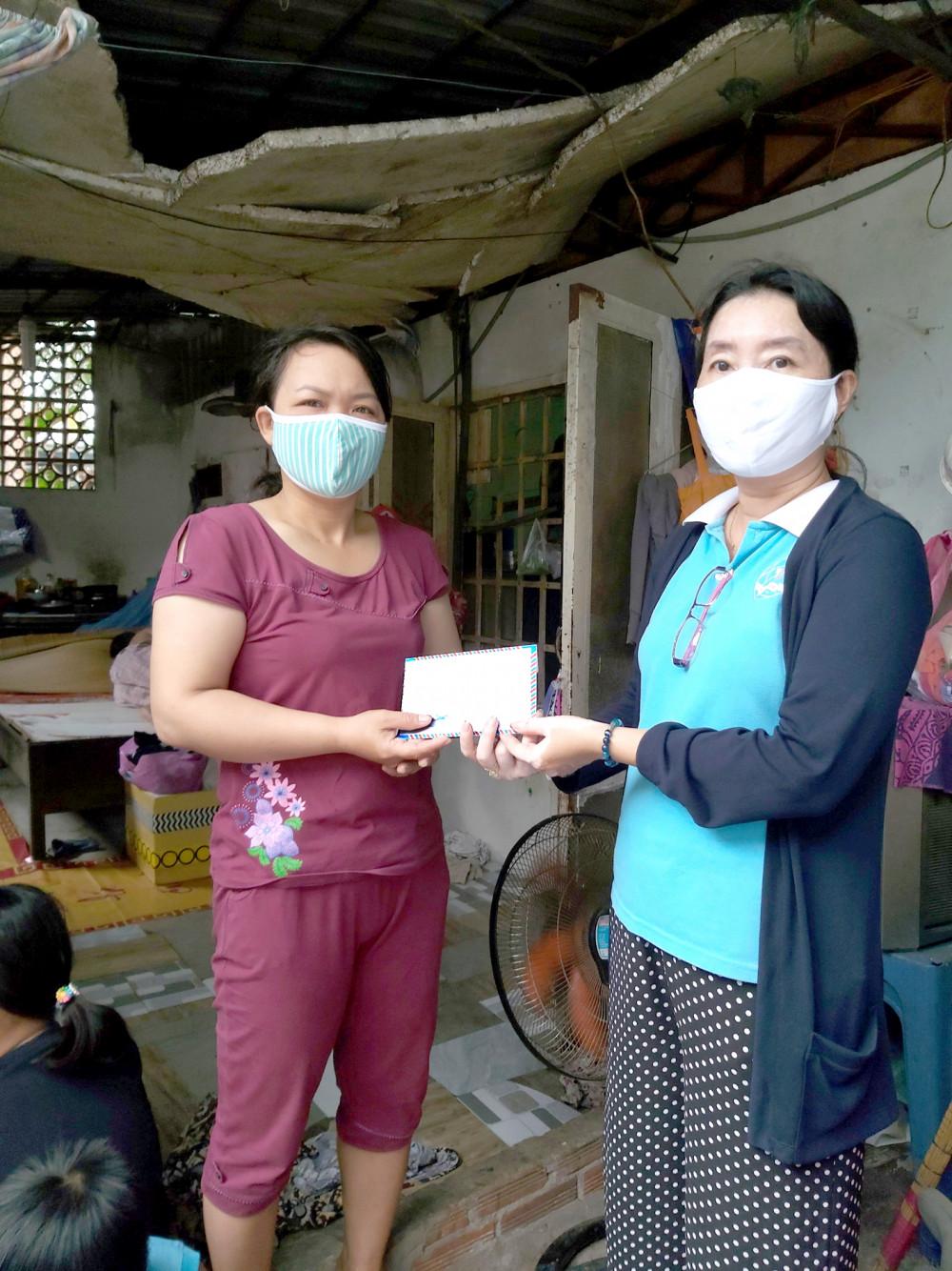 Chị Đoàn Thị Kim Ngoan (phải) - Chủ tịch Hội LHPN P.Phước Bình - trao tiền hỗ trợ nhà trọ cho chị Thái