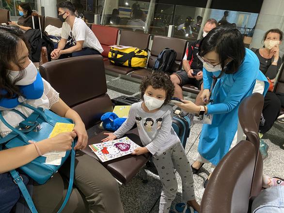 Tiếp viên tiến hành đo thân nhiệt cho hành khách tại sân bay Nội Bài- Ảnh: VNA