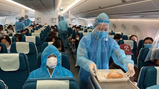 Tiếp viên mặc đồ bảo hộ kín kẽ trong lúc phục vụ cho hành khách về nước- Ảnh: VNA