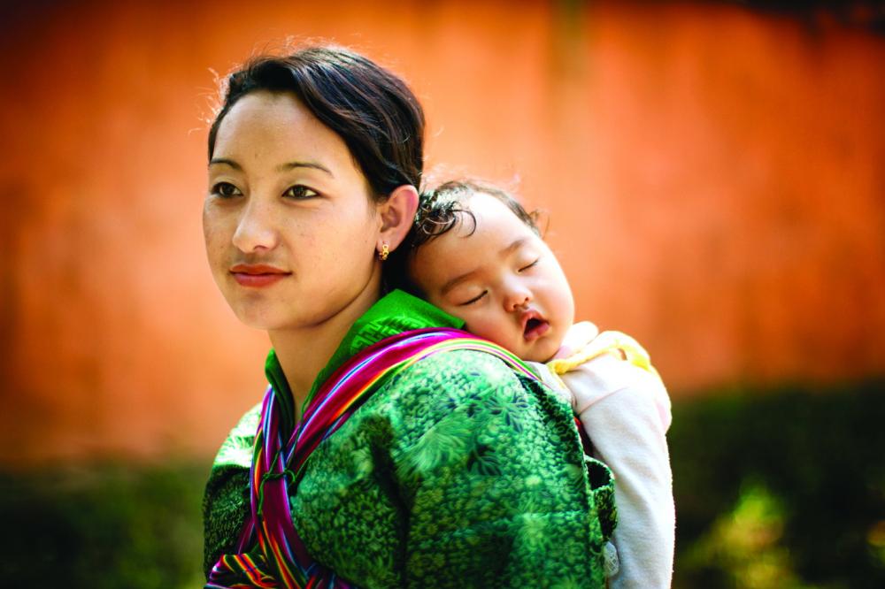 Không gian và thời gian lắng đọng khi con say giấc trên lưng mẹ. Bức ảnh chụp trong khung cảnh yên ắng ở Bhutan hòa quyện cùng khoảnh khắc mà muộn phiền chẳng thể ghé ngang của mẹ và con - Ảnh: Getty Images