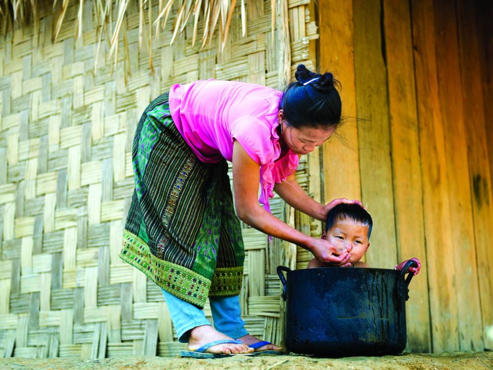 """Người mẹ dân tộc H'Mông ở Lào đang tắm cho con trai nhỏ. Chiếc nồi quen thuộc của gia đình được tận dụng làm """"bồn tắm di động"""" cho cậu bé. Hình ảnh đơn sơ, bình dị nhưng sẽ là phần ký ức khó xóa nhòa của cậu bé. Đó là phần ký ức đẹp đẽ khi em có mẹ bên cạnh chăm sóc, dưỡng nuôi - Ảnh: Getty Images"""