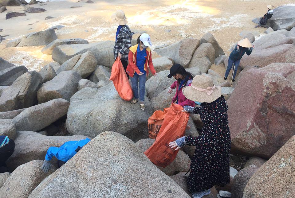 nhóm tình nguyện viên phải mạo hiểm leo trèo, chui vào các khe đá để nhặt nhiều mảnh rác bị gió thổi dắt bên trong