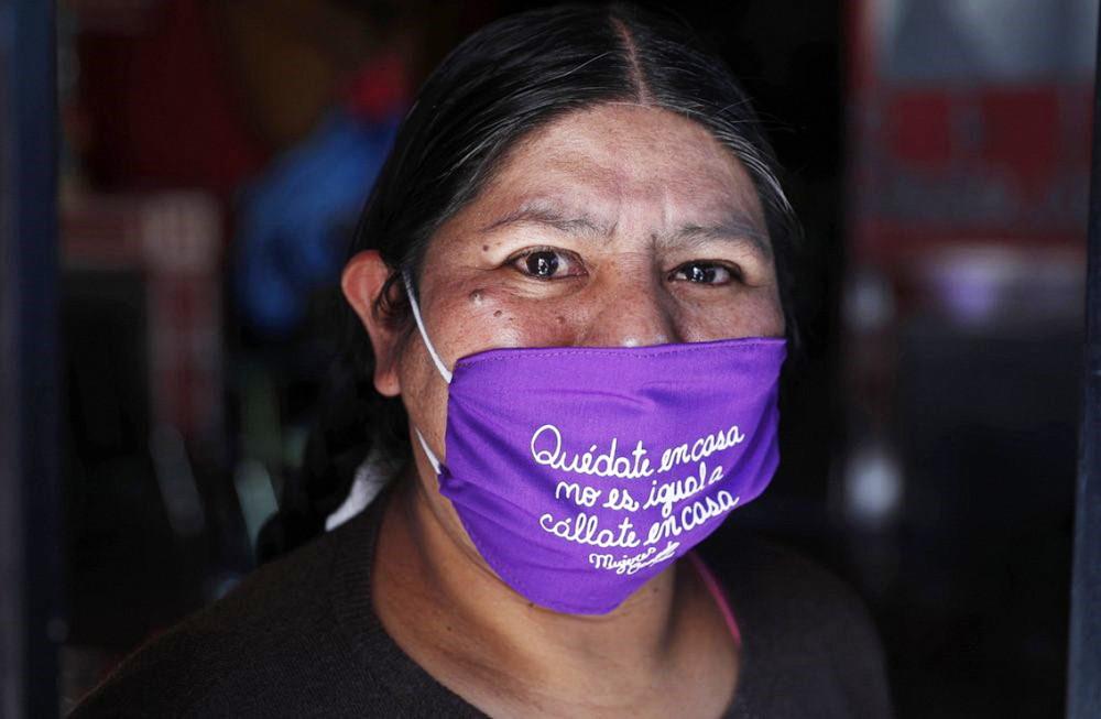 """Emiliana Quispe, thành viên tổ chức nữ quyền địa phương Soones Creando ở La Paz (Bolivia) chụp ảnh với khẩu trang có dòng chữ Tây Ban Nha """"Ở nhà không có nghĩa là im lặng"""" - Ảnh: AP"""