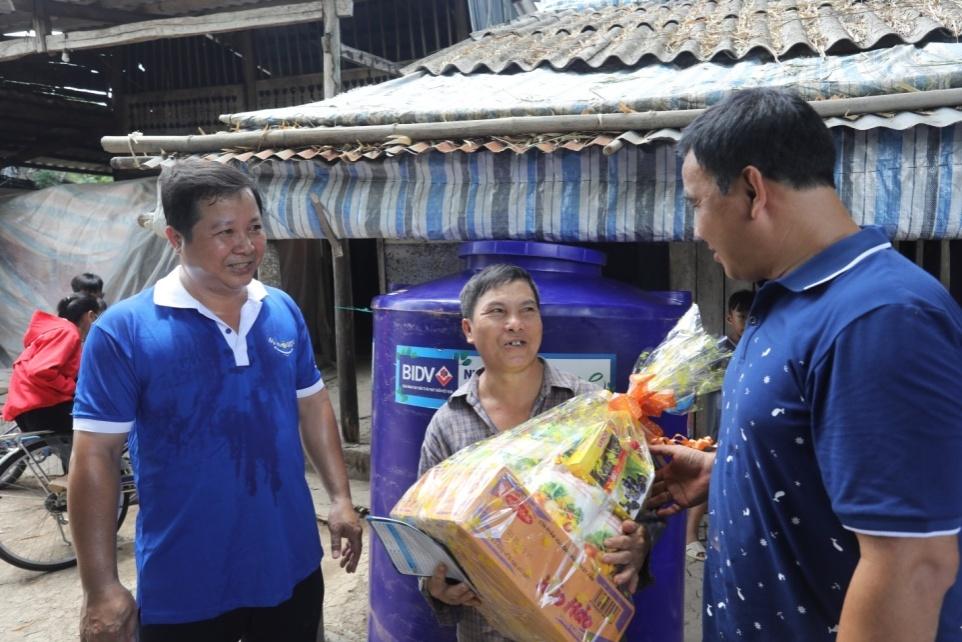 Anh Lê Huỳnh – Phó giám đốc BIDV Cà Mau cùng nghệ sĩ Quyền Linh trao tặng quà và bồn chứa nước cho người dân. Ảnh: BIDV cung cấp