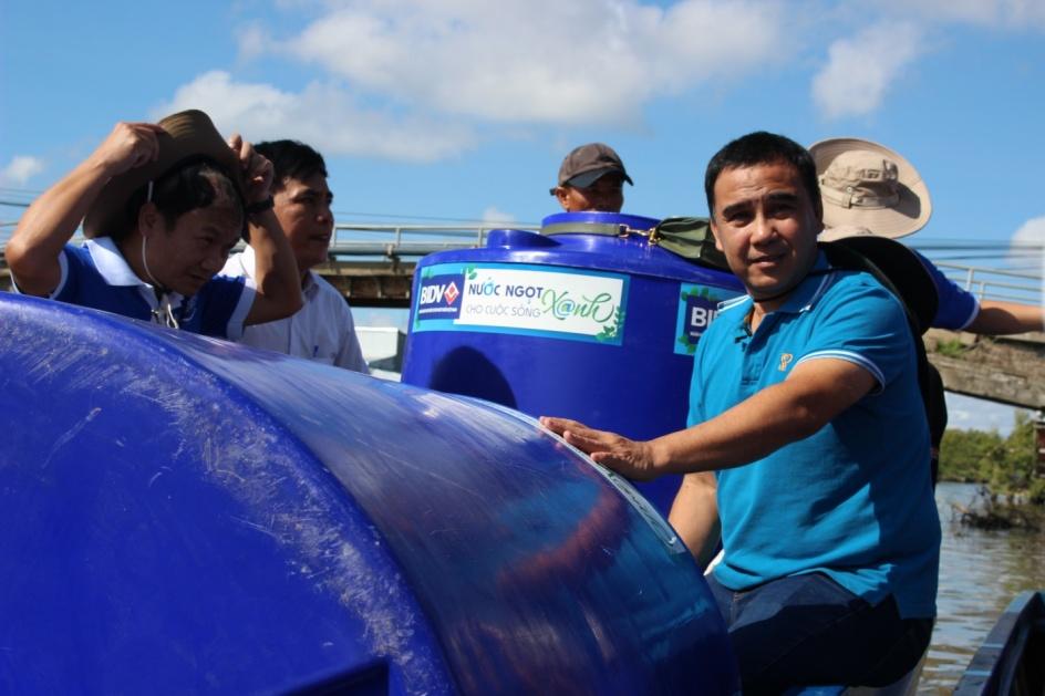 Từng thành viên BIDV không quảng ngại đường xa, di chuyển bằng vỏ lãi đem bồn chứa nước tặng bà con tại An Biên, Kiên Giang. Ảnh BIDV cung cấp