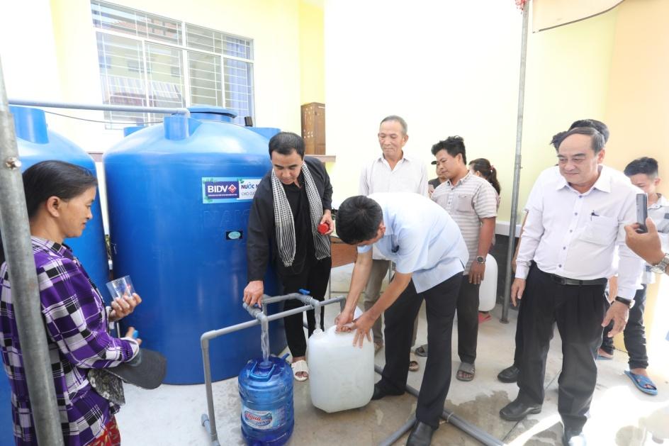 Nhiều người dân Long An vui mừng hứng nước ngọt từ máy lọc nước do BIDV lắp đặt. Ảnh BIDV cung cấp