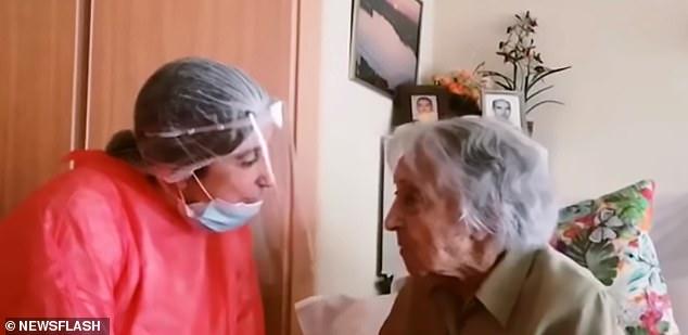 Bà Maria Branyas trò chuyện cùng một người chăm sóc trong bộ đồ bảo hộ.