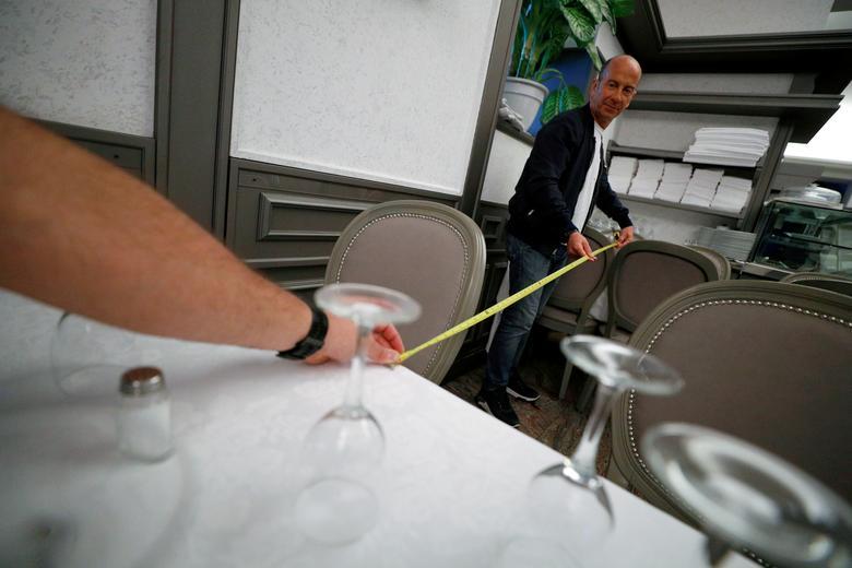 Fabio Andreotti và Alberto Iannelli, chủ nhà hàng Nuova Fiorentina (Rome, Ý) sử dụng thước dây để đo khoảng cách giữa các bàn hợp lý theo quy định.
