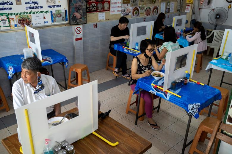 Một nhà hàng mì ở Thái Lan sử dụng những tấm chắn trên bàn để duy trì giãn cách xã hội. Tấm chắn được chừa một khoảng trống, lót bằng nhựa trong để hai bên có thể nhìn thấy nhau.