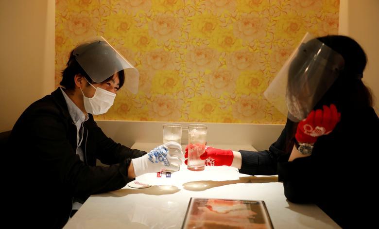2 thực khách mang khẩu trang, đeo găng tay và mang mặt nạ tại một nhà hàng ở Tokyo, Nhật Bản. Đất nước mặt trời mọc là một trong những quốc gia bị ảnh hưởng khá nặng từ dịch COVID-19.