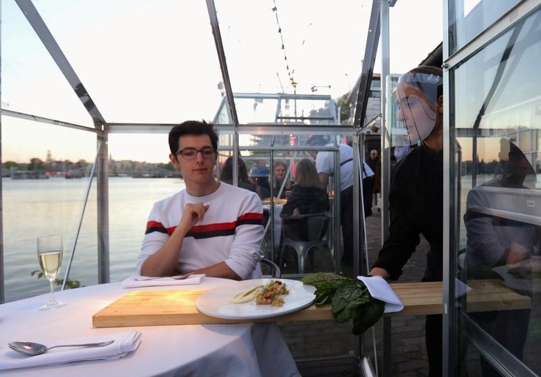 Nhân viên đưa thức ăn đến thực khách thông qua một tấm ván gỗ dài để duy trì khoảng cách an toàn.