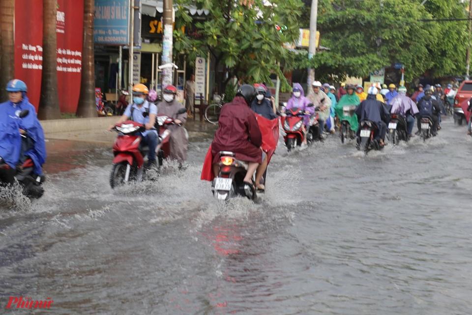 Người dân bì bõm lội nước ngập về nhà sau mưa dông mạnh