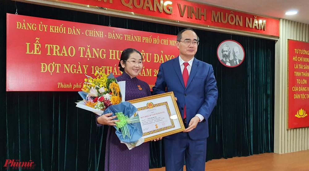 Bí thư Nhân chúc mừng tặng hoa Phó Bí thư Võ Thị Dung nhận huy hiệu 40 năm tuổi Đảng.