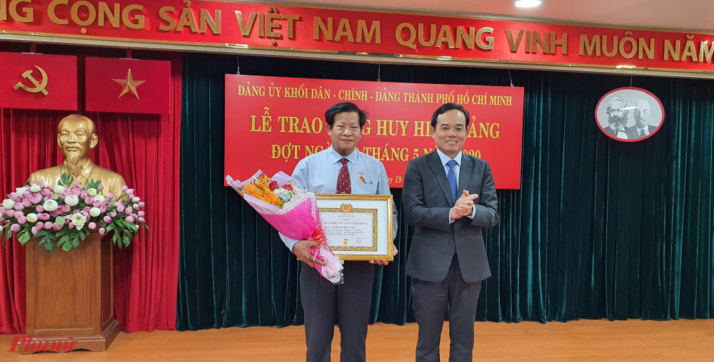 Phó bí thư Thường trực Trần Lưu Quang trap huy hiệu 45 năm tuổi Đảng cho ông Nguyễn Đức Sáu, đảng viên Chi bộ Hội Luật gia Thành phố