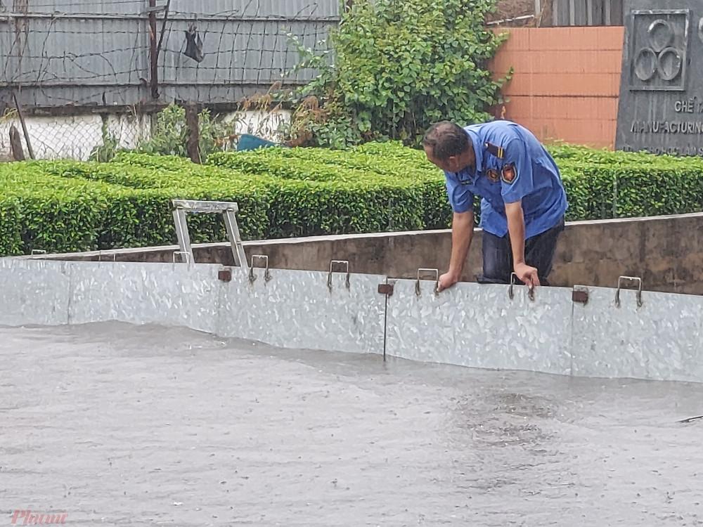 Nước ngập ngày càng cao, nhân viên bảo vệ phải đội mữa giữ tấm chắn không cho nước ngập xô ngã.