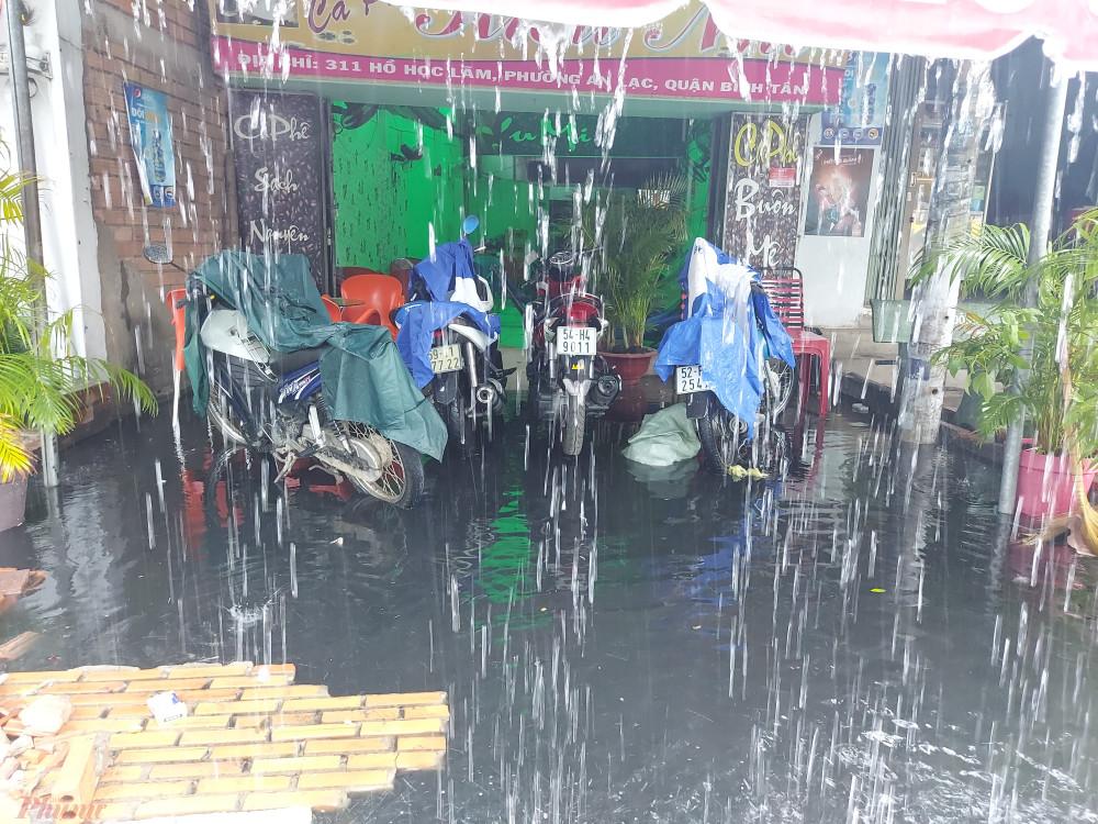 Một quán cà phê bị dòng nước đen kịt tràn vào lênh láng.