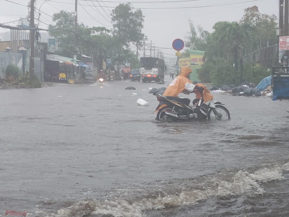 """Nhiều đoạn nước ngập sâu, xe chết máy nên người dân phải vất vả dắt xe vượt qua """"rốn ngập""""."""