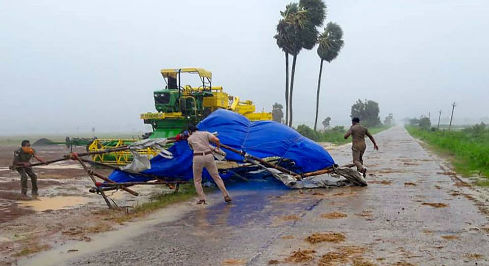 Lực lượng cảnh sát Ấn Độ hỗ trợ dọn dẹp đường giao thông sau khi bão đi qua.