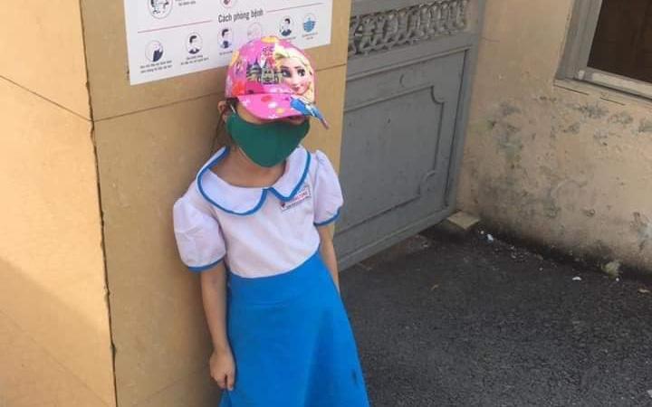Hình ảnh cháu bé đến trường sớm và phải đứng ngoài trời nóng