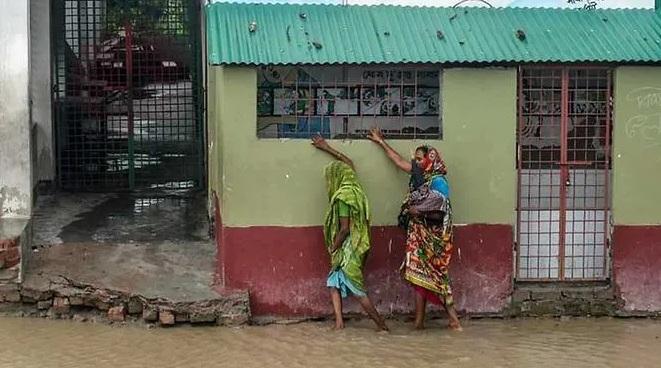 Người dân khu vực Dacope, thành phố Khulna, Bangladesh vượt qua những con đường ngập nước để đến nơi trú ẩn.