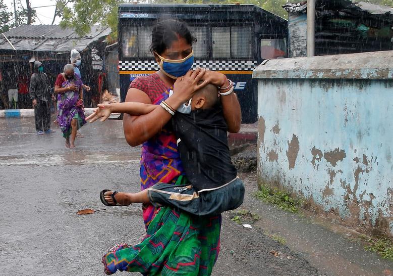 Người phụ nữ ở Kolkatar ôm con trai chạy khỏi khu ổ chuột để tìm nơi tránh trú an toàn giữa cơn mưa nặng hạt kèm theo gió lốc mạnh.