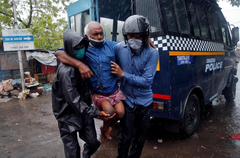 Người đàn ông tàn tật ở Kolkatar được cảnh sát hỗ trợ đưa đến nơi trú ngụ an toàn từ một khu ổ chuột.