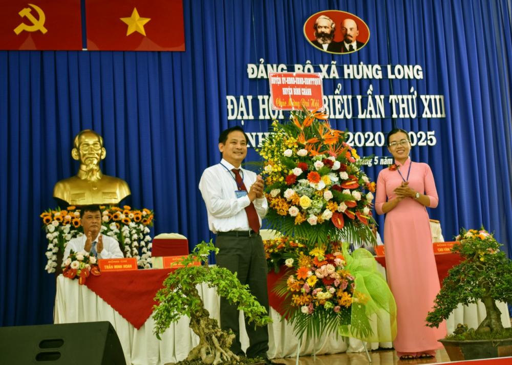 Bà Trần Thị Cẩm Thúy- Bí thư Đảng ủy xã Hưng Long nhận hoa của Huyện ủy H, Bình Chánh chúc mừng đại hội