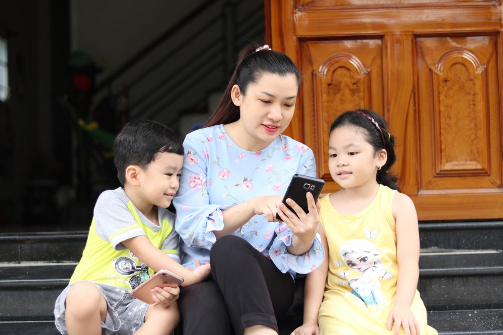 Chị Nguyễn Thị Anh Thy, một phụ huynh ở phường Linh Đông dành thời gian xem phim hoạt hình, những bức ảnh gia đình cùng con để bé cảm thấy vui vẻ.